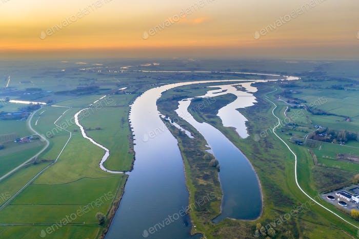 Lowland river IJssel through sunset landscape