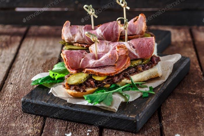Delicius Sandwiches mit geräuchertem Schweinefleisch, Gurken und Zwiebel auf einem schwarzen Holzbrett