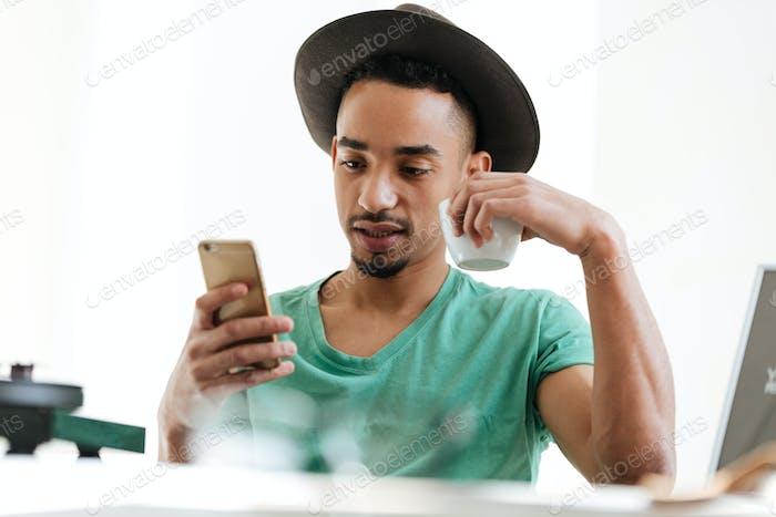 Afrikanischer Mann in T-Shirt mit Smartphone