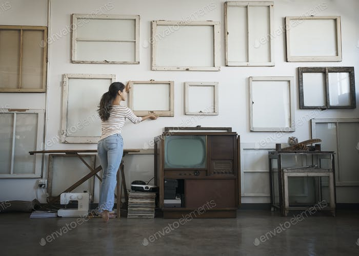 Loft decor. A woman hanging picture frames, blank canvases on a wall.