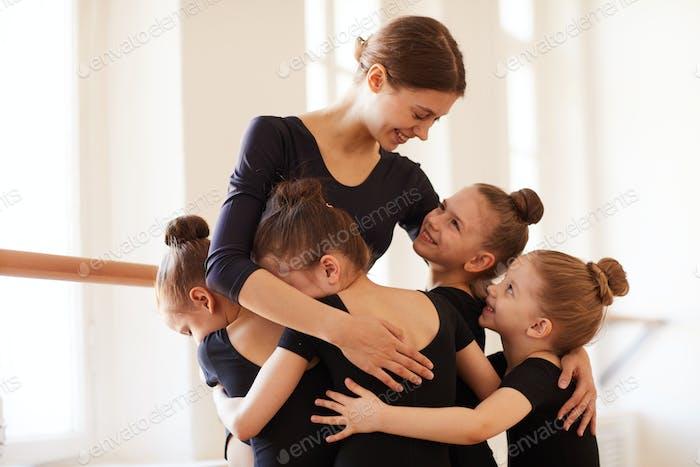 Kids Hugging Ballet Teacher