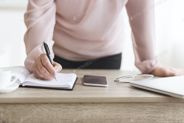 Senior woman writing down tasks for day