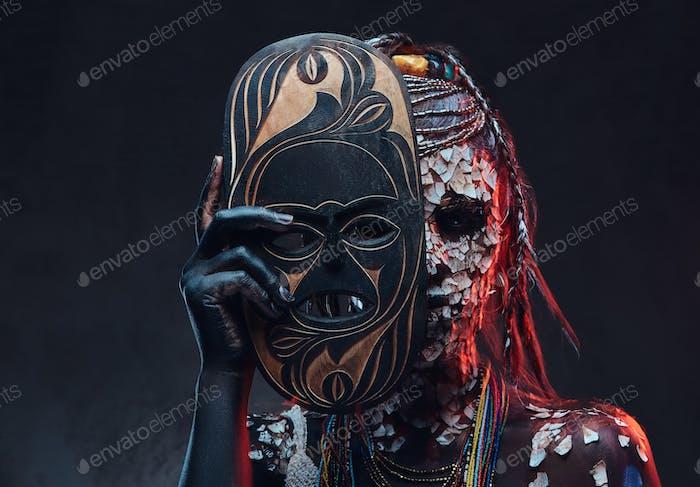 Porträt einer gruseligen afrikanischen Schamanin mit einer versteinerten rissigen Haut und Dreadlocks