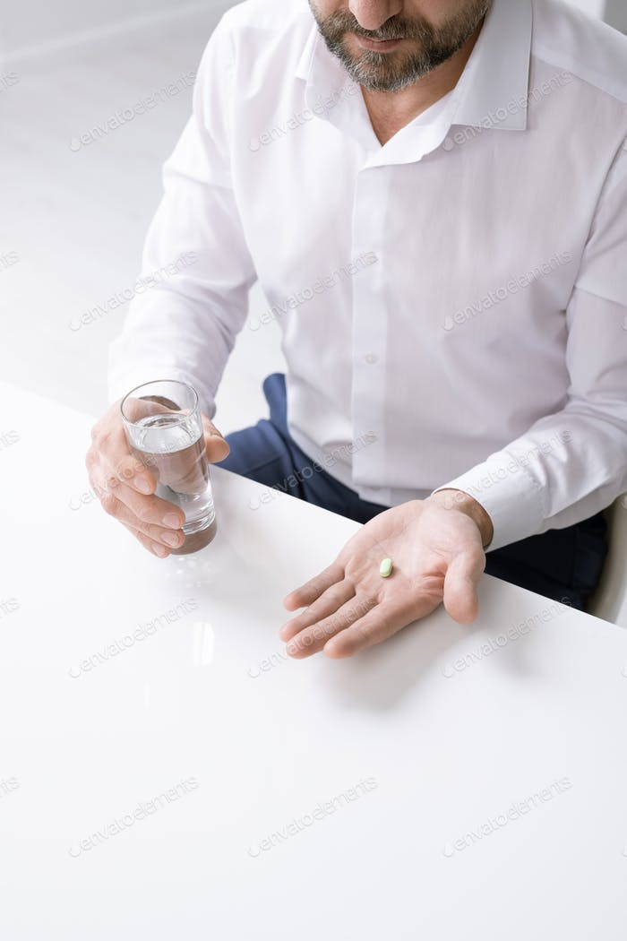 Hands of bearded businessman with headache holding pill and glass of water