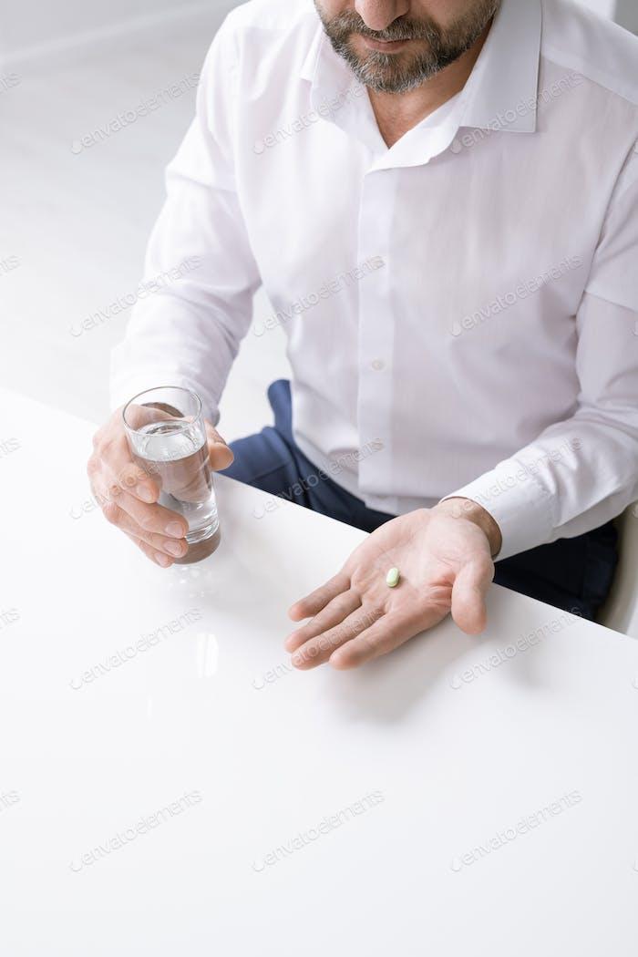Руки бородатого бизнесмена с головной болью, держа таблетки и стакан воды