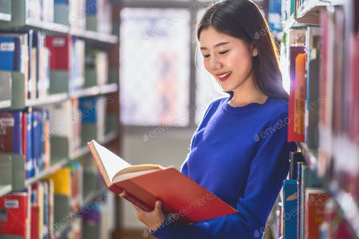 Asian young Student in casual suit standing and reading the book at book shelf in library