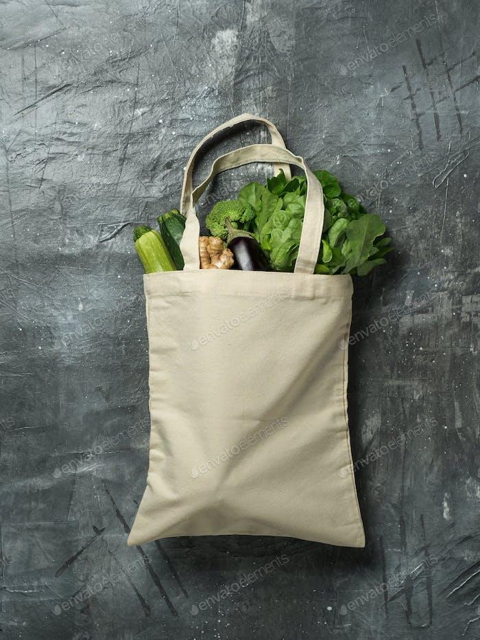 Baumwollbeutel mit Gemüse auf grauem Hintergrund