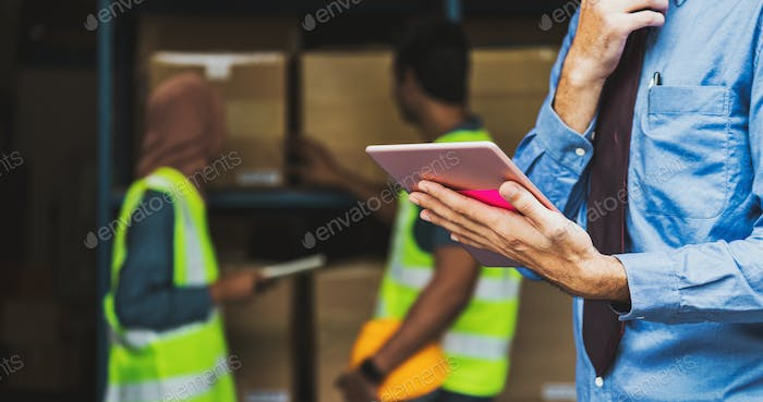 Closeup Manger hand using digital tablet over Idian worker man working with Muslim worker