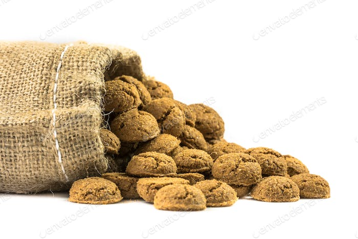 Traditional pepernoten treats in jute bag on white background