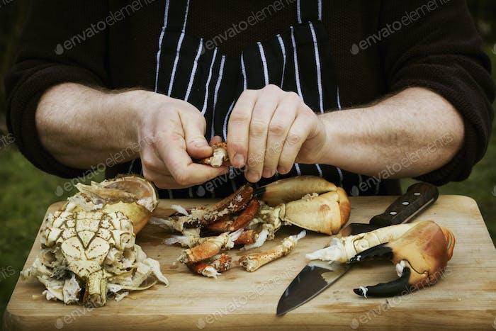 Nahaufnahme von einem Koch, der eine Krabbe zubereitete.