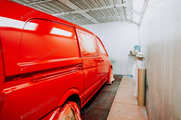 Red minivan in painting booth. Automotive building indudstry