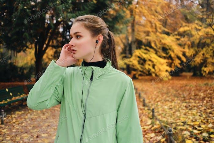 Seitenansicht der attraktiven Läufer Mädchen hören Musik in Kopfhörer im Park