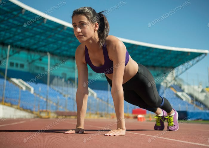 track and field woman doing press up exercise