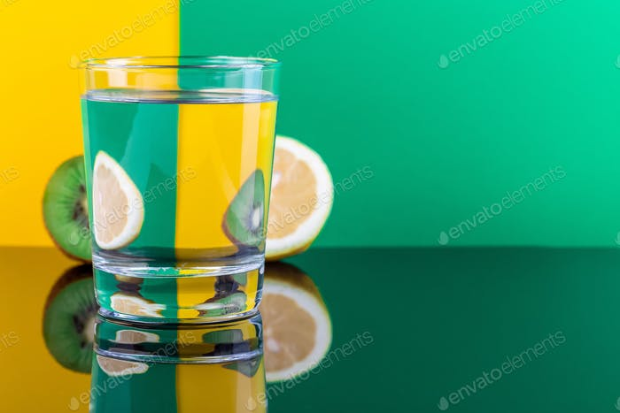 Optical illusion with kiwi and lemon distorted through glass of water