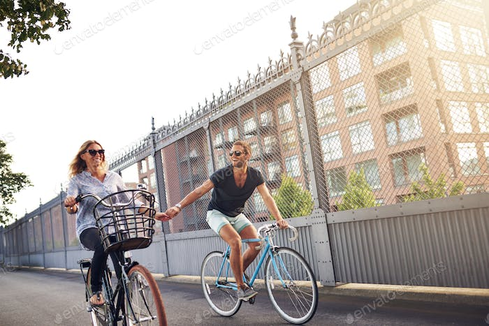 Romantic couple holding hands as they go cycling