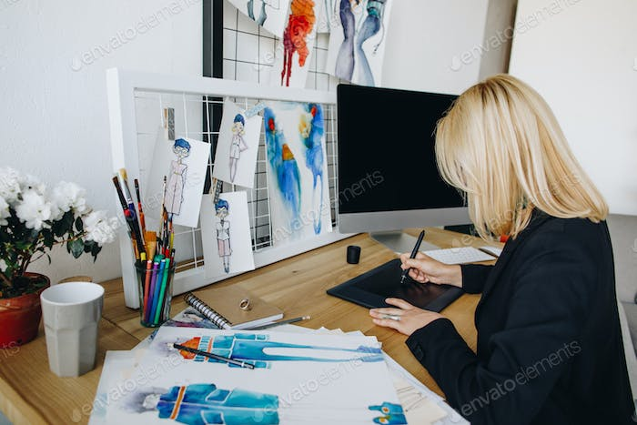 side view of young female fashion designer drawing on graphic tablet at workplace