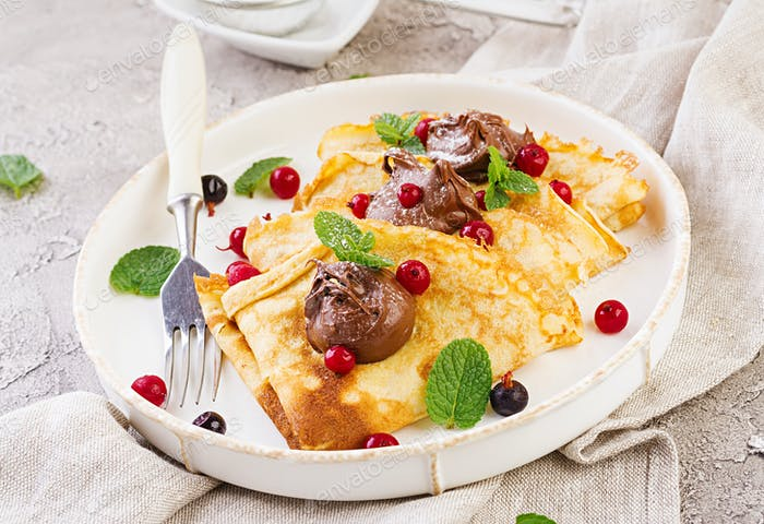 Pancakes with berries and chocolate decorated with mint leaf. Tasty breakfast.