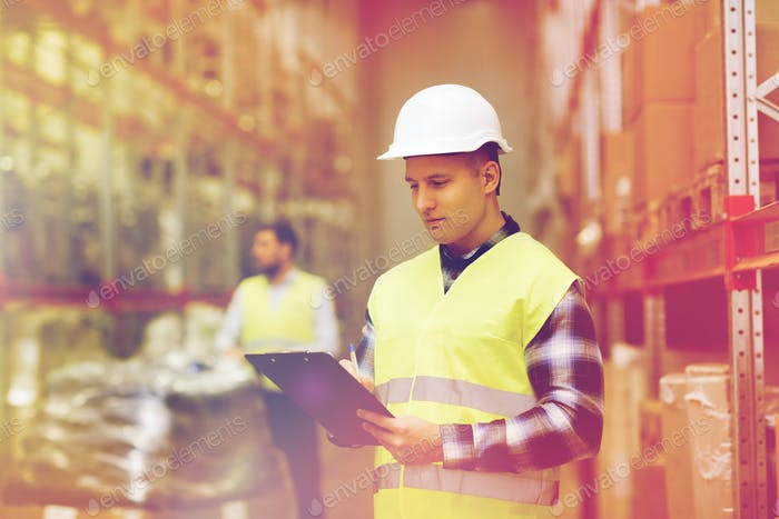 man with clipboard in safety vest at warehouse