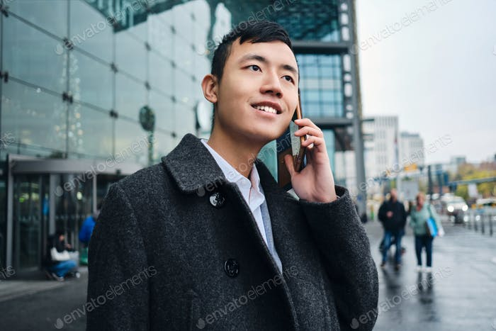 Young attractive Asian businessman happily talking on smartphone