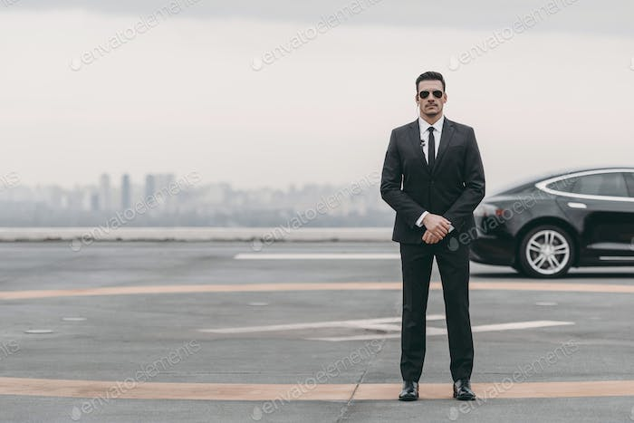 serious bodyguard standing with sunglasses and security earpiece on helipad and looking at camera