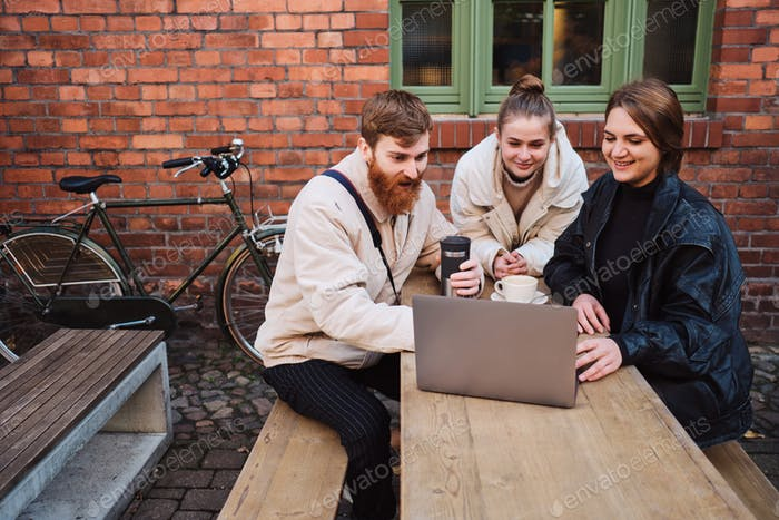 Group of attractive friends joyfully working on laptop during coffee break in cafe outdoor