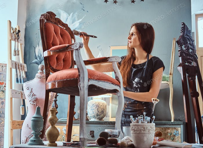 Female artist painting vintage chair in white color with paintbrush in workshop.