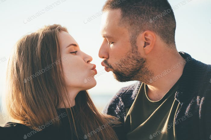 Man looking tenderly at woman and kissing. Young couple stands embracing