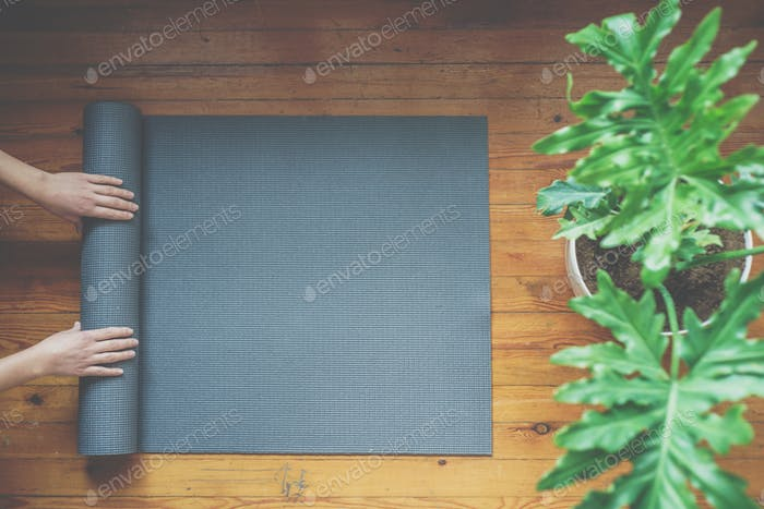 Woman rolling her mat after a yoga class, top view