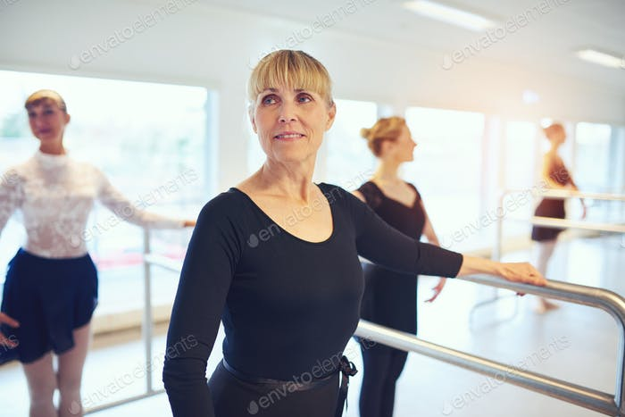 Adult ballerina practicing gymnastics in class and smiling