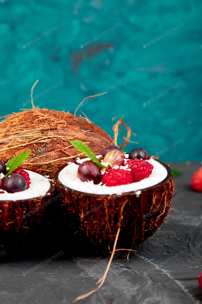 Fruit salad agrus, gooseberry, rasbberry in coconut shell bowl