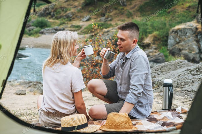 Happy young couple travelers in casual outfits kissing near tent in mountains