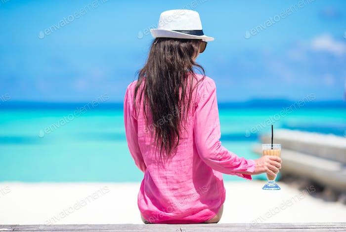 Beautiful young girl relaxing near the swimming pool