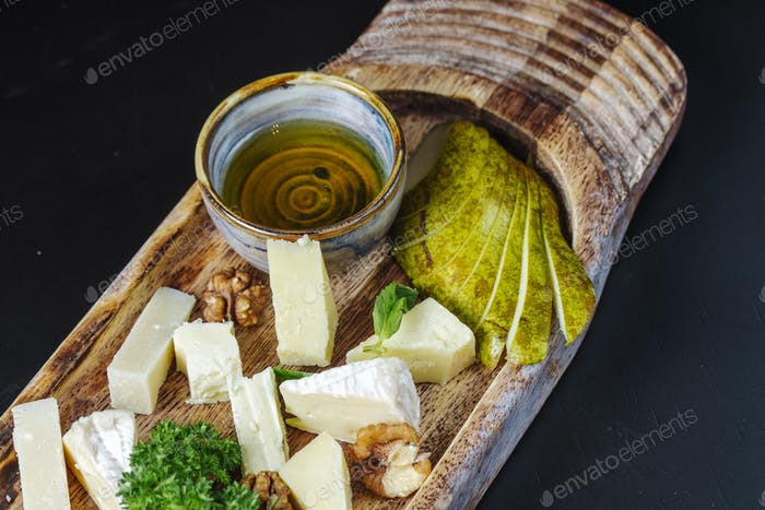 side view sliced roquefort cheese with herbs nuts and honey on a wooden plate