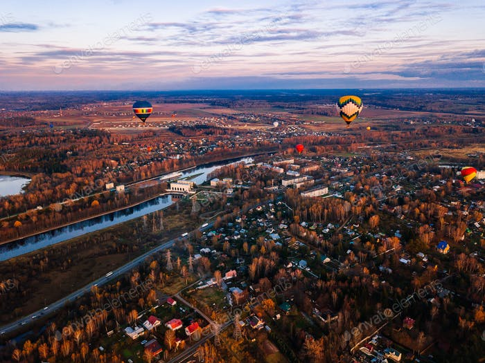 Aerial view of colorful hot air balloon is flying at sunset over the town in autumn season