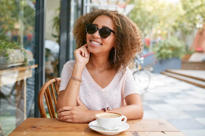 Cute young girl sitting at outdoor cafe