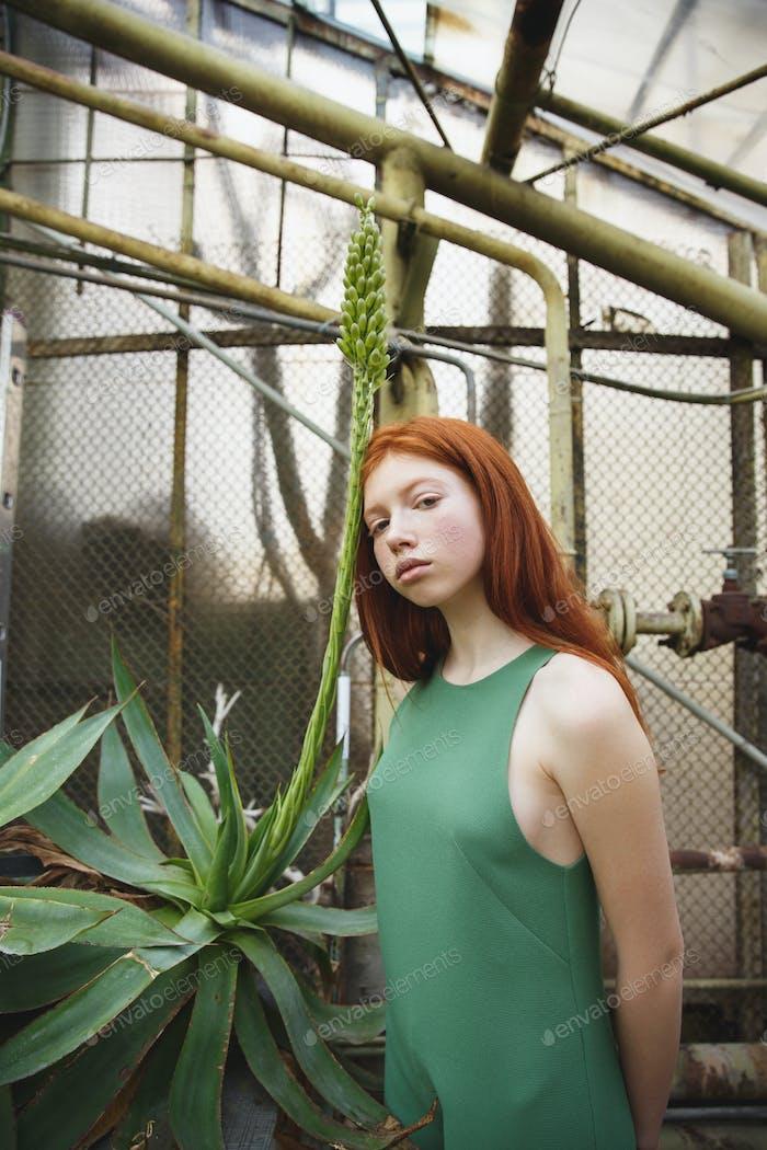 Wonderful girl lean on green exotic plant in greenery