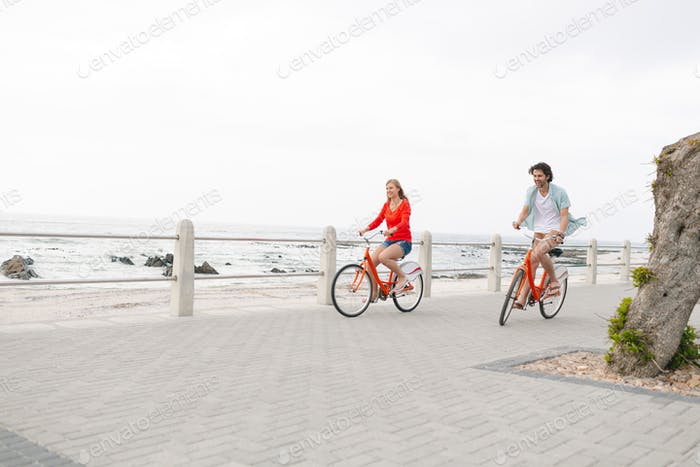 Side view of young Caucasian couple riding bicycle on pavement near promenade at beach