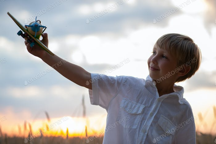 Boy in a  white shirt with a plane in hands against sky. Kid hol