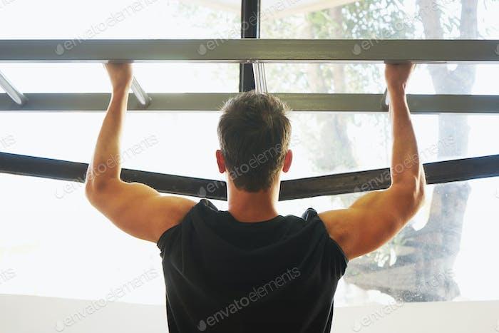 Deportista muscular fitness modelo masculino tirando hacia arriba en barra horizontal