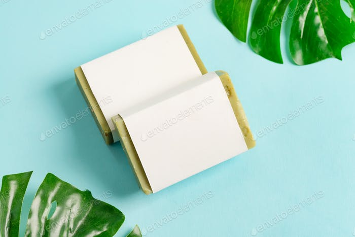 Olive handmade herbal natural soap bar from organic plant with paper label on a tropical leaf and