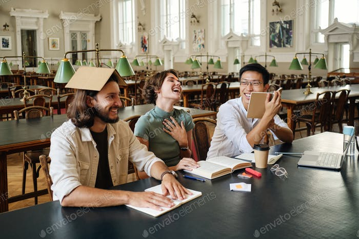 Group of happy multinational students joyfully fooling around studying together in library