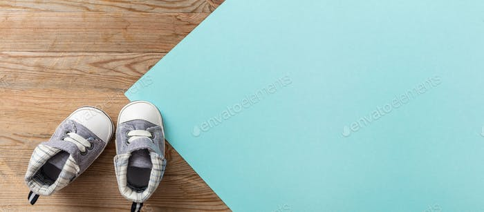 Baby boy shoes on pastel blue and wooden background, banner