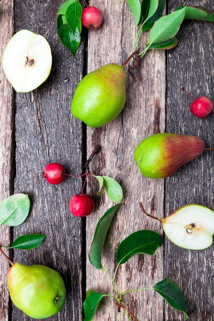 Birne und kleiner Apfel auf rustikalem Holzhintergrund.