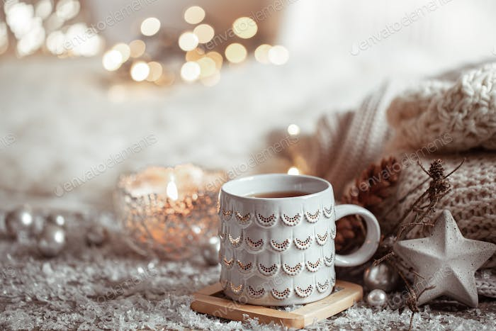 Cozy winter background with a beautiful cup, decor details and bokeh copy space.