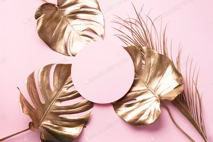 Golden tropical monstera leaf on pink background with copy space. Top view. Flat lay. Creative