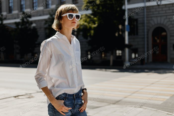 Stylish young woman in white sunglasses dressed in white shirt and jeans is standing in the city