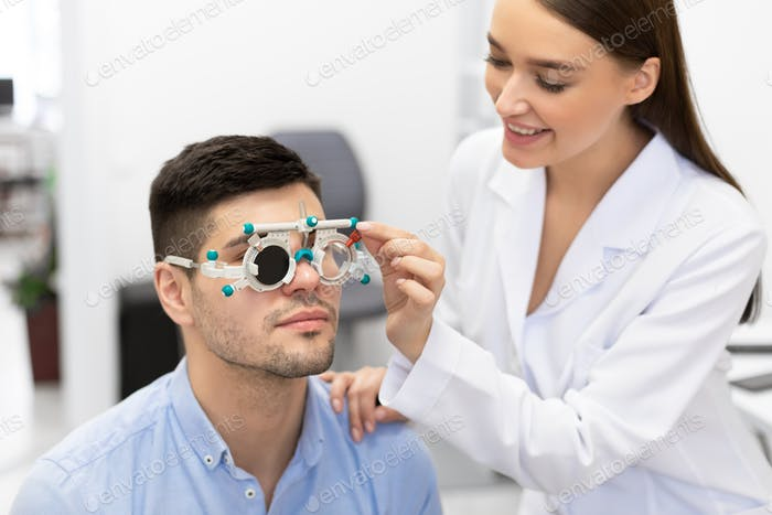 Optometrist checking patients vision with trial frame