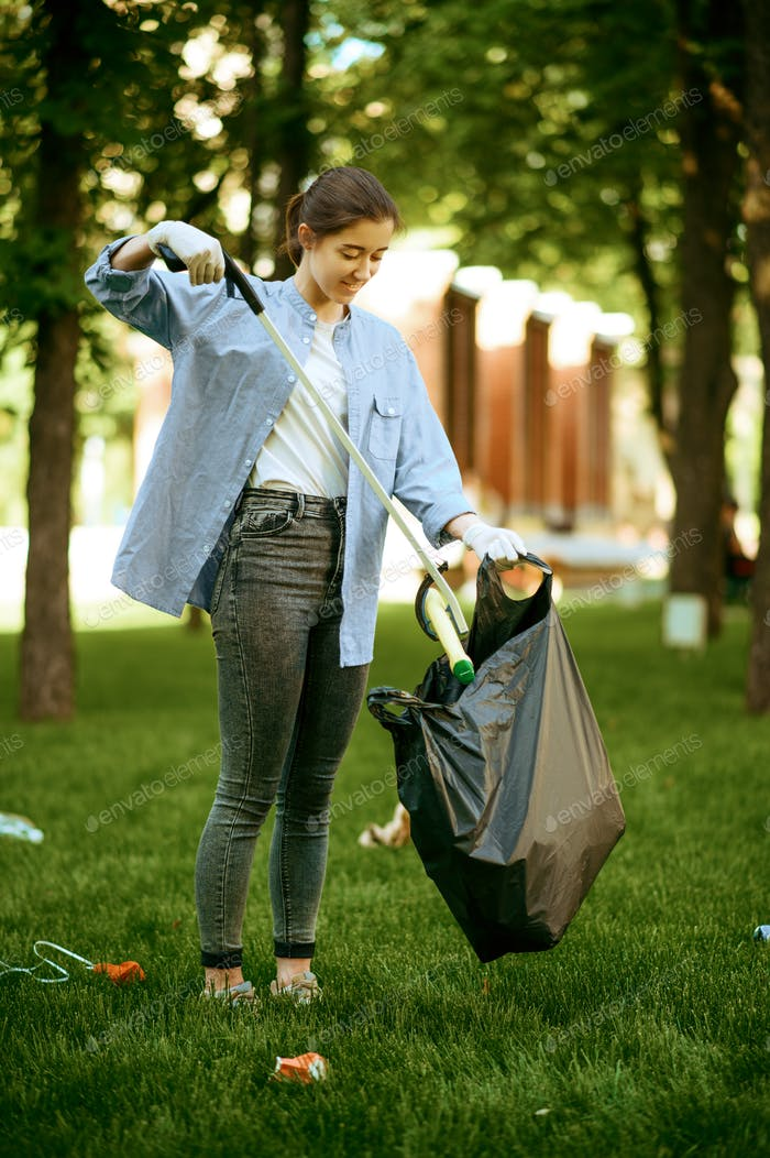 Young woman collects garbage in plastic bag