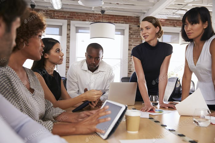Businesspeople Meeting Around Table In Modern Office
