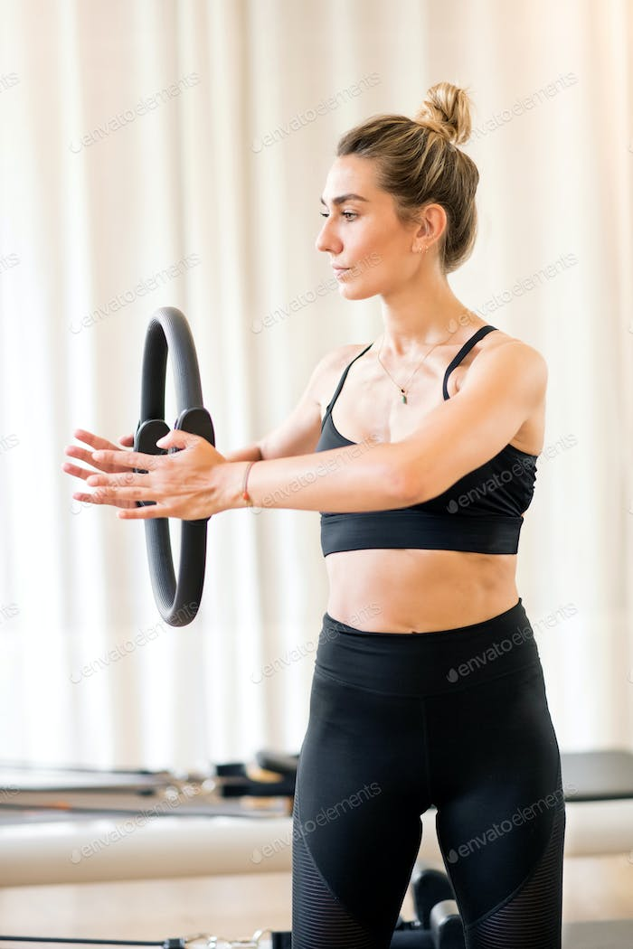 Young woman using magic circle for arm work